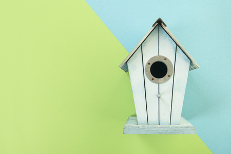 Blue wooden bird house on a blue and green background with copy space