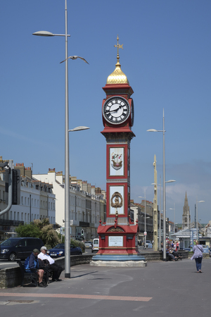 Weymouth, Dorset, England - May 24 2018: Jubilee clock tower on a sunny day with clear blue sky with tourist walking on the boulevard