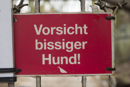 Red warning sign on a gate to warn in the german language for a biting dog who guards the premisis
