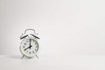 Vintage white alarm clock on a design white background with space for copy with the time on eight oclock Banco de Imagens
