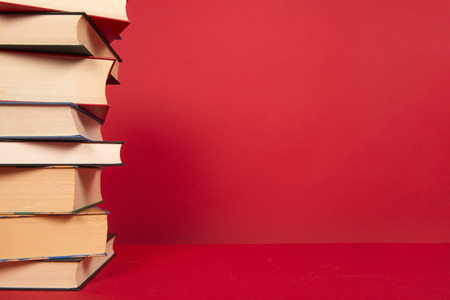 Stack of books in the corner on a red background
