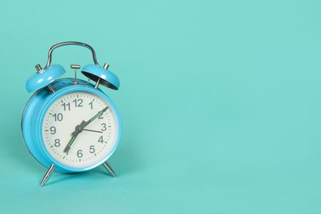 Reloj retro azul sobre un fondo azul con espacio de copia