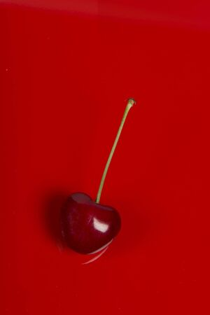 Single red cherry with stem on a red background in a vertical image