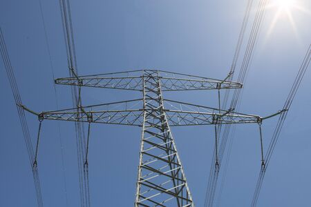 Electricity mast seen from a low angle on a background on a blue sky with sunbeams