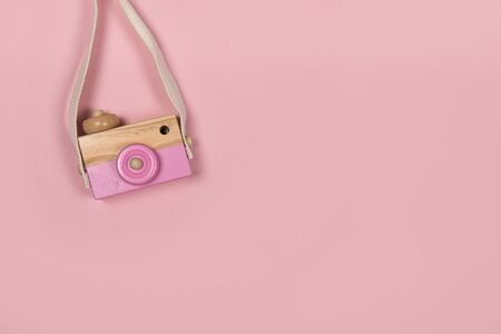Wooden toy camera on a pink background with copy space
