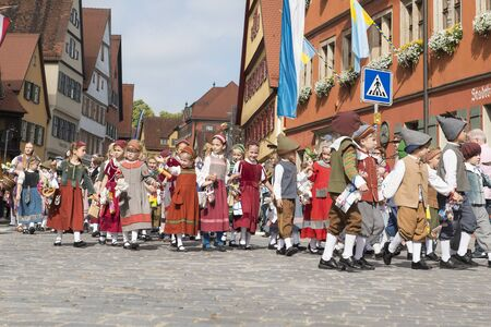 Dinkelsbühl, Germany - July 16, 2019; Young children in the centre of Dinkelsbühl during the festivities of the historical Kinderzeche, where the childeren celebrate the end of the school year