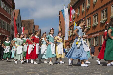 Dinkelsbühl, Germany - July 16, 2019; Young adults in colorful dresses in the centre of Dinkelsbühl during the festivities of the historical Kinderzeche, where the childeren celebrate the end of the school year 新聞圖片