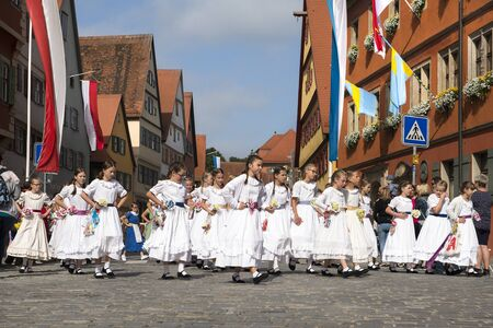 Dinkelsb hl, Germany - July 16, 2019; Children in white dresses in Dinkelsb?hl during the festivities of the historical Kinderzeche, where the painting celebrate the end of the school year