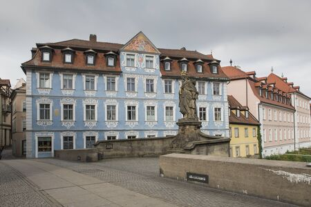Bamberg, Germany - July 15, 2019; Statue of Queen Kunigunde and a blue house on the Alte Rathaus bridge in Bamberg