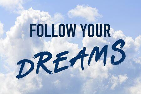 Phrase follow your dreams on a blue clouded sky