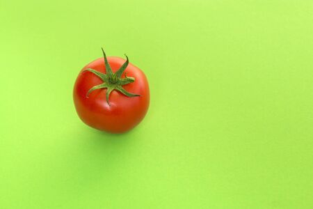 Single real tomato seen at its top on a green background