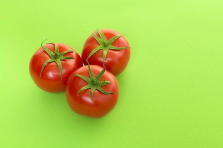 Three red real tomatos seen at its top on a green background
