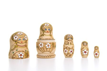 Set of five wooden matryoshka dolls standing in a row, from large to small isolated on a white background