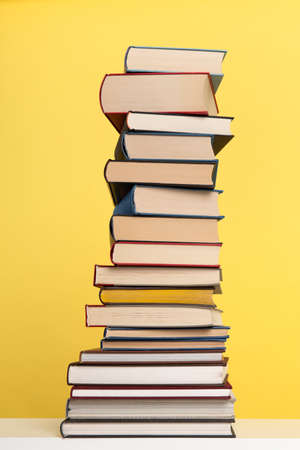 Pile of books stacked on a yellow background with space for copy in a vertical image