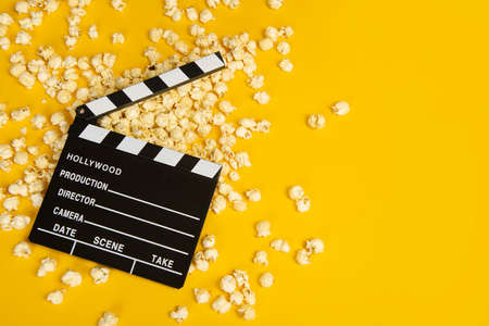 Movie clapperboard and popcorn on a yellow background as a concept for movies with space for copy
