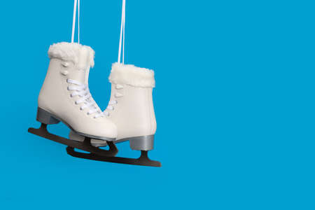 Pair of white figure ice skates on a blue background with space for copy