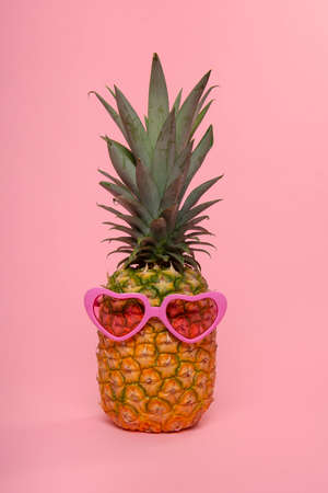 Funny pineapple with pink heart shaped glasses on a pink background 版權商用圖片
