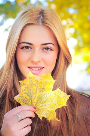秋のメープル ツリーの葉を持つ少女 写真素材