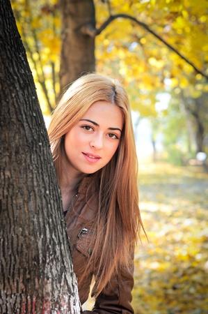 happy woman in park hiding behind a tree