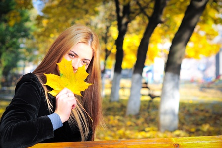 Girl with maple tree leaf in autumn