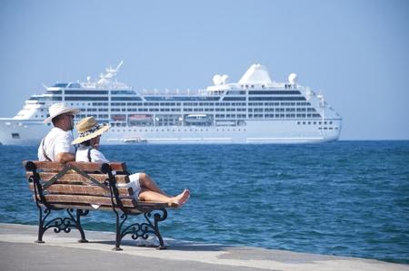 (クレタ島) での休暇カップル ハニア地中海でベンチに座って、クルーズ船を見てします。2011 年夏