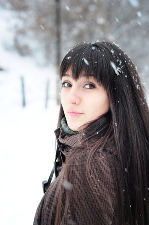 Young woman winter portrait outdoors in snow, turning towards the camera