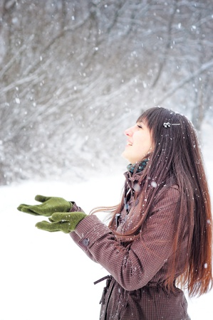 Beautiful woman in warm clothing outdoor in snowy weather  catching snowflakes Stock Photo