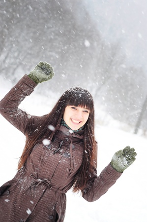 Beautiful woman in warm clothing outdoor in snowy weather  catching snowflakes photo