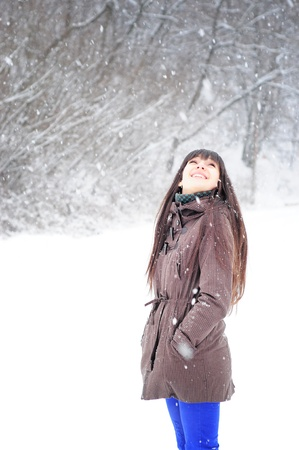 Beautiful woman in warm clothing outdoor in snowy weather  smiling looking up