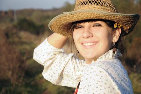 麦わら帽子の農村少女の笑みを浮かべてください。