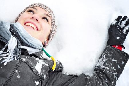 雪の天使を作る雪に横たわっている冬の服装と若いブルネットの女性 写真素材