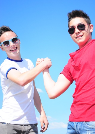 Two teenage boys shaking hands against blue sky