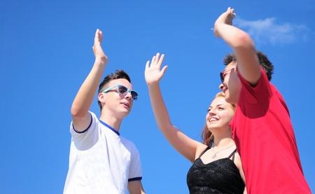 Drei glückliche Freunde Teenage Jungen und Mädchen, was eine fünf, im Freien gegen blauen Himmel im Sommer