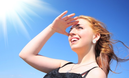 青い空と太陽の下で笑顔の美しい若い女性