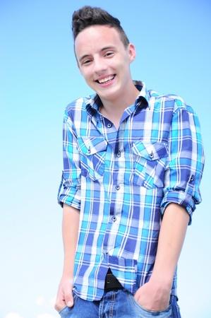 Porträt eines kühlen Teenager-Jungen mit den Händen in den Hosentaschen, vor blauem Himmel