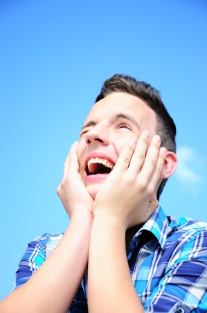 looking upwards: Teenage boy excited, looking upwards holding his hands around face