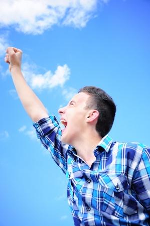 Teenage Junge schreiend siegreich mit erhobenem Arm