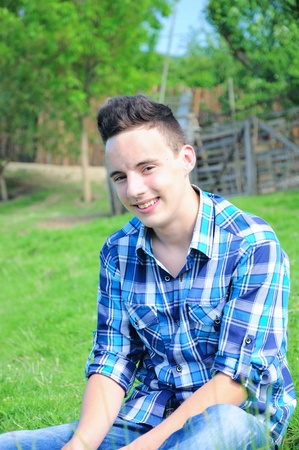 Nette junge teen boy Verlegung im Gras lächelnd