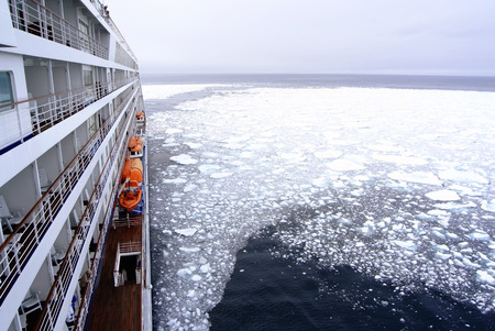 arctic waters: Cruise Ship bow passing icy snow arctic waters near Spitsbergen Svalbard Norway.