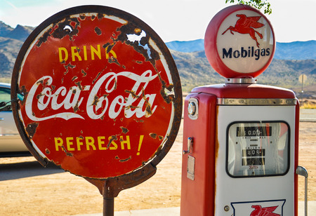 advertizing: Retro gas pump and a rusty coca-cola sign on historic route 66 in Arizona on May 15, 2013