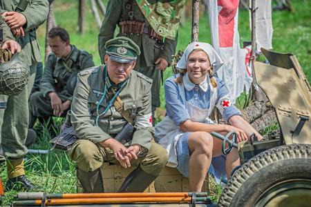 luitenant: Tekov, SLOWAKIJE - juli 26,2014: Duitse luitenant en een verpleegkundige op een pauze tijdens de re-enactment van de Tweede Wereldoorlog vecht in Slowakije Redactioneel