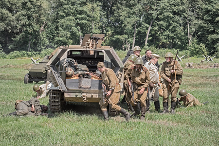 squad: STARY TEKOV, SLOVAKIA - JULY 26,2014:  Squad of soviet soldiers capturing a german troop carrier during Reconstruction of a World War II fight. Editorial