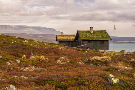 Cabin with turf roof near Hardangervidda National Park with Sloddfjorden lake in the background, Buskerud county, Norway