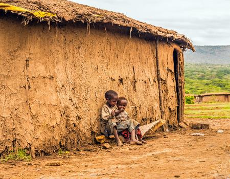 MAASAI MARA, KENYA - OCTOBER 17, 2014 : Two african boys sitting in front of a Masai tribe village house