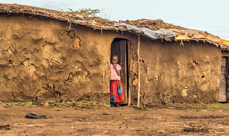 MAASAI MARA, KENYA - OCTOBER 17, 2014 : Young african girl from masai tribe in the doorway of her home. The Maasai are a Nilotic ethnic group living in southern Kenya and northern Tanzania