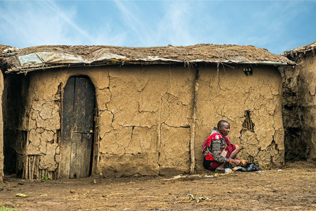 maasai: MASAI MARA, KENYA - OCTOBER 17, 2014: African woman from Masai tribe working in front of her village house. The Maasai are a Nilotic ethnic group living in southern Kenya and northern Tanzania