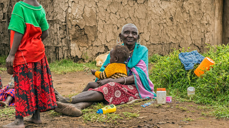 northern african: MASAI MARA, KENYA - OCTOBER 17, 2014: Old African woman from Masai tribe holding a baby in her village. The Maasai are a Nilotic ethnic group living in southern Kenya and northern Tanzania