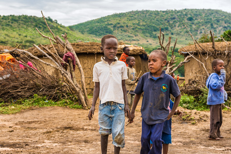 northern african: MASAI MARA, KENYA - OCTOBER 17, 2014: Two african boys from Masai tribe in their village. The Maasai are a Nilotic ethnic group living in southern Kenya and northern Tanzania Editorial