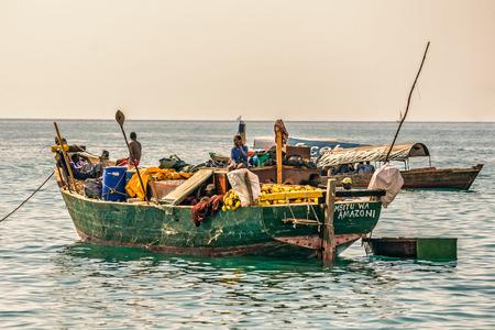 pescador: Stone Town, Zanzibar - 24 de octubre 2014: Los pescadores locales en un barco tradicional en la costa del Oc�ano �ndico cerca de Stone Town. Stone Town es una parte de la ciudad de Zanz�bar, la capital de Zanz�bar, Tanzania.