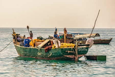 STONE TOWN, ZANZIBAR - OCTOBER 24, 2014: Local fishermen on a traditional boat at the shore of Indian ocean near Stone Town. Stone Town is a part of Zanzibar City, the capital of Zanzibar, Tanzania.